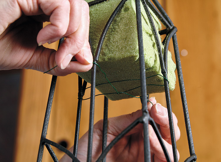 Attach floral foam to your bird-feeding obelisk: Using floral wire, attach a block of floral foam inside the top of the obelisk.