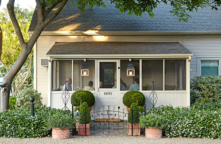 cozy-garden-lead: Just a handful of containers makes a big impact in a small space. Flanking the sidewalk with topiaries in containers calls attention to the front door.