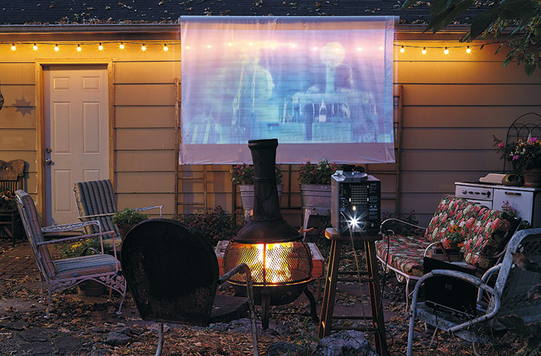 budget-friendly-outdoor-movie-night:Turn your backyard into a theater and save money by staying home and watching a DVD on a projector.