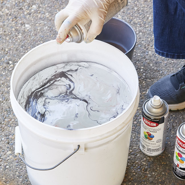 spray-surface-with-paint: Work quickly spraying layers of paint onto the surface of the water.