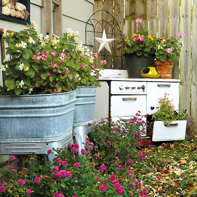Upcycled wash bins and vintage stove for garden art and planting: Easy-to-grow wax begonias (Begonia semperflorens) fill up these old wash tubs. For just a few dollars, you can pick up a couple packs of plants at the garden center and have flowers from spring through frost.