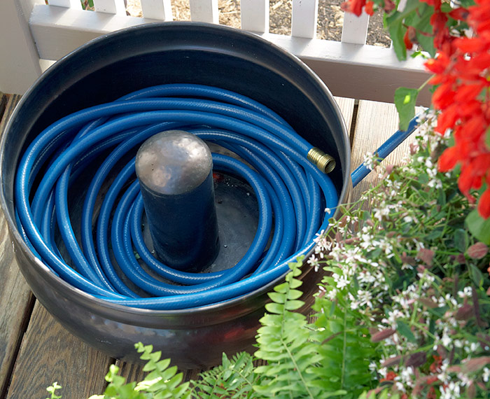 good-way-to-store-hose:This decorative hose holder keeps the hose under control and looks good, too. Some styles come with a lid, so they can sit out near the faucet without filling with rain water.