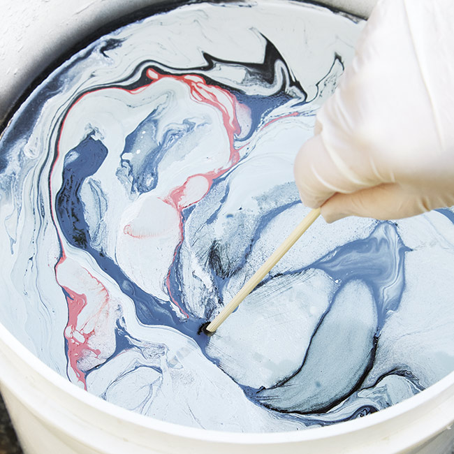 marbleize-surface-with-skewer: Swirl the paint colors together with a skewer to achieve a marbled effect.