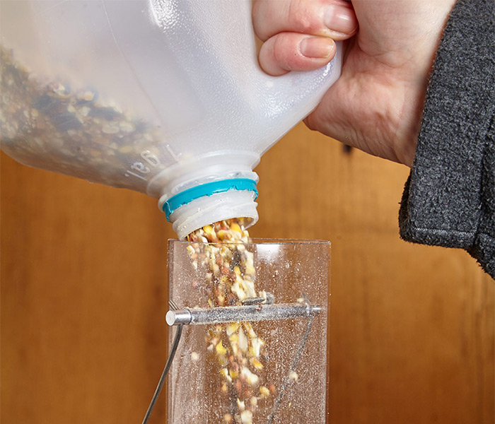 Easily refill bird feeders with this DIY Scoop: Remove the milk jug cap and the birdseed flows easily into this tube feeder.