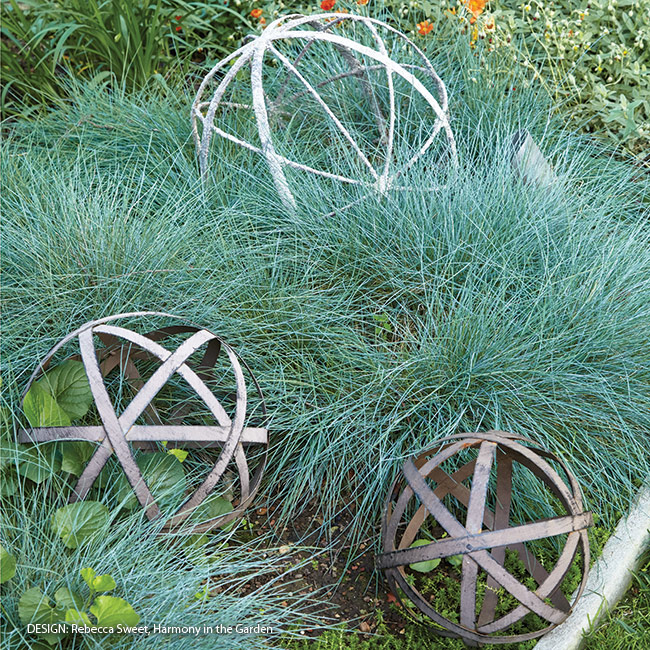 Adding-structure-to-your-garden-using-unique-objects: In among this airy grass, these metal orbs take on even more interest than they might set in any other garden spot. And a grouping makes a bigger impact than one alone would.