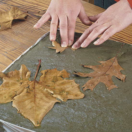 Press leaves into concrete: Use a variety of leaf shapes and sizes to add variety and interest to the design.
