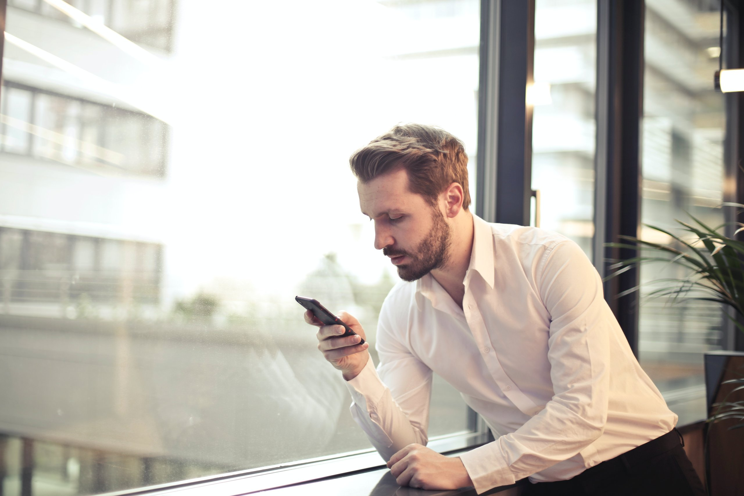 photo-of-man-in-white-dress-shirt-holding-phone-near-window-859265 (1)