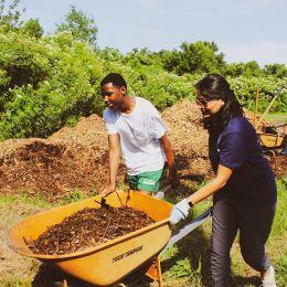 Lockton Associates pushing a wheelbarrow for charity