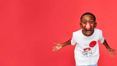 Young boy smiling excitedly and wearing a red nose.