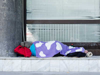 A homeless woman sleeping on the ground