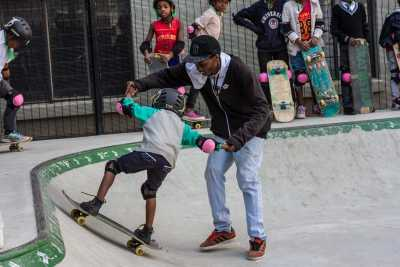 A man helps a child skateboard
