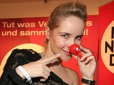 Red Nose Day, Germany Smiling woman pointing to her red nose