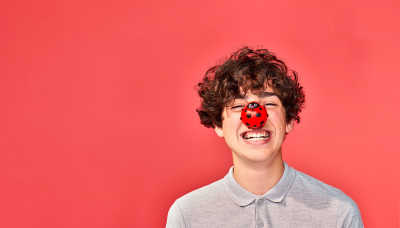 A boy laughing and wearing a red nose in the shape of a ladybird.