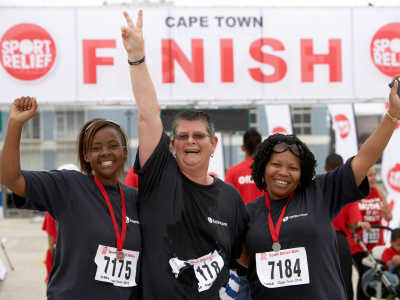 3 cheering runners at the Sport Relief fun-run in Cape Town