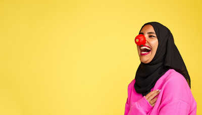 A woman laughing and wearing a red nose.