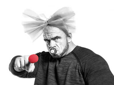 Nose Day, Finland, Bald muscly guy with a bow in his hair, dummy in his mouth and a red nose on his pointing finger