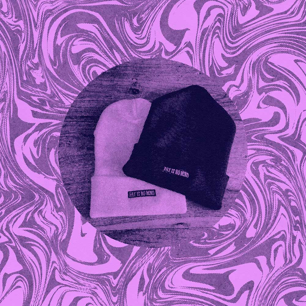 """Two beanie style hats on a wood table with """"Pay It No Mind"""" printed on the front"""