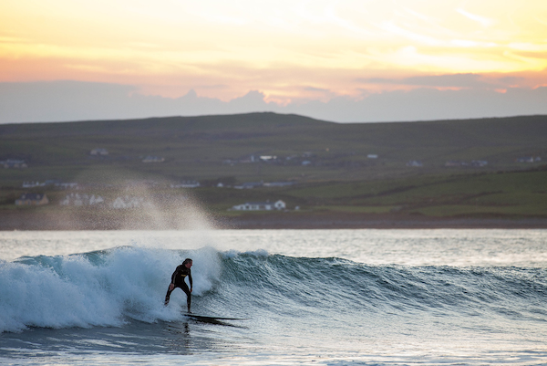 A surfer rides a wave with a sunset behind him in Ireland