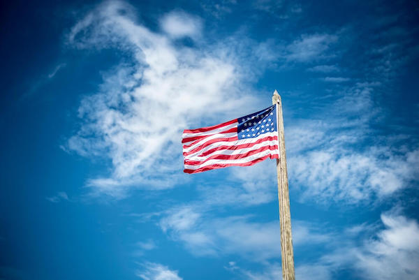 An American flag with a blue sky background.