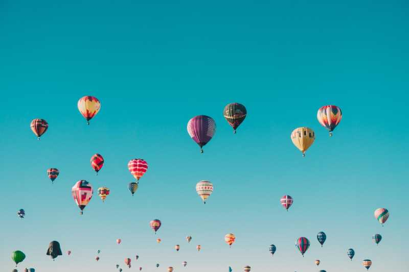 Dozens of hot air balloons against a blue sky