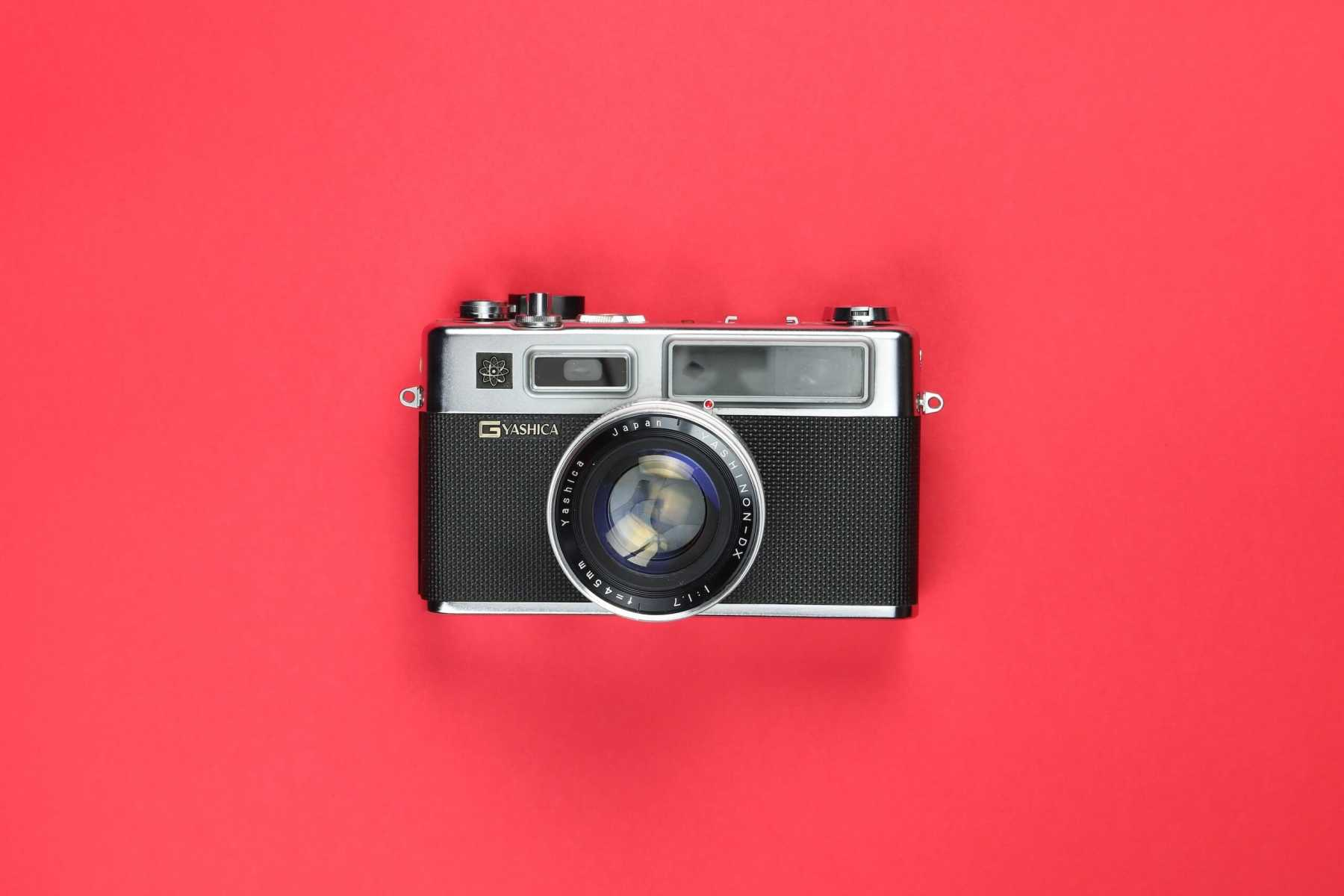 A vintage camera on a red background.